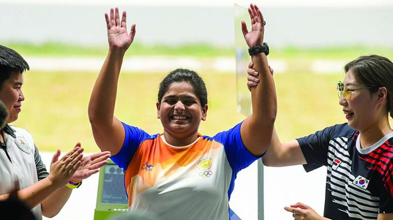 Gold medallist Rahi Sarnobat (left) of India is ecstatic as bronze medal winner Kim Minjung of Korea raises her hand after the women's 25m pistol event at Palembang on Wednesday. 	(Photo: PTI)