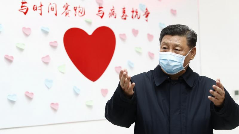 In this Feb. 10, 2020 photo released by Xinhua, Chinese president Xi Jinping gestures near a heart shaped sign and the slogan 'Race against time, Fight the Virus' during an inspection of the Centre for Disease Control and Prevention in Chaoyang District in Beijing. As the rest of the world grapples with a burgeoning virus outbreak, China's ruling Communist Party has turned to its propaganda playbook to portray its leader as firmly in charge, leading an army of health workers in a