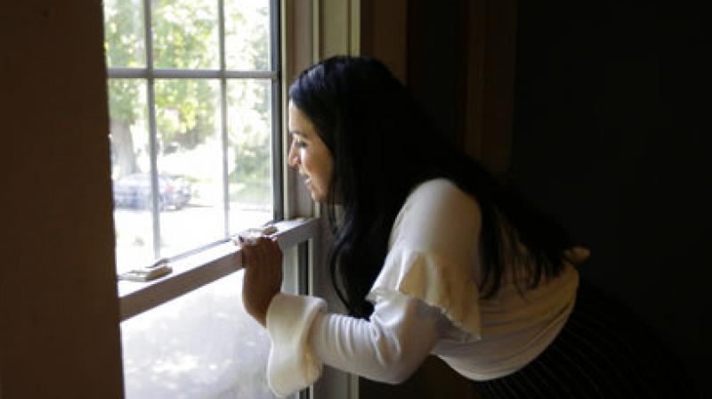 In this Wednesday, Aug. 30, 2017, photo, Ninotska Love, who has been accepted at Wellesley College, looks out a window in her dorm room at the women's school in Wellesley, Mass. (Photo: AP)