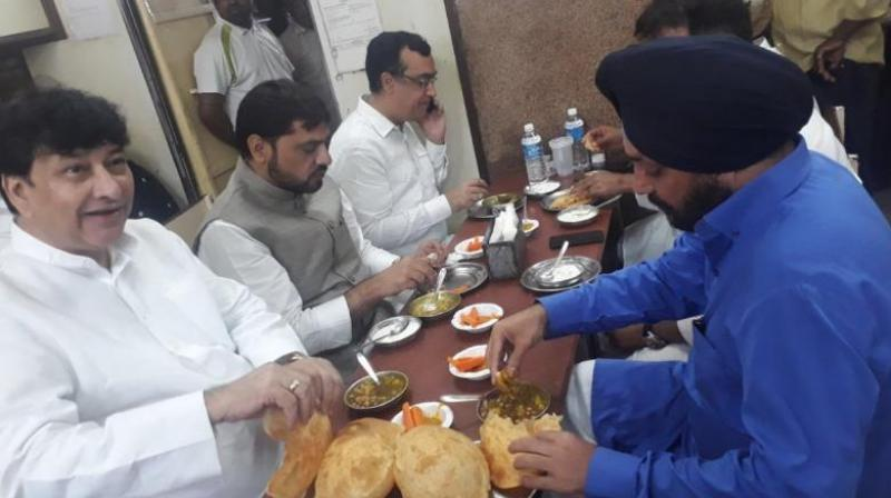 As the protest started, an image of Congress leaders including Ajay Maken, Haroun Yusuf and Arvinder Singh Lovely, gobbling down chhole bhaturas and other Delhi delicacies at a popular restaurant started doing the rounds. (Photo: ANI | Twitter)