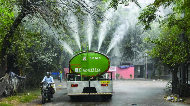A tanker sprays water to curb rising pollution at Gautam Puri in New Delhi on Tuesday. (Photo: PTI)
