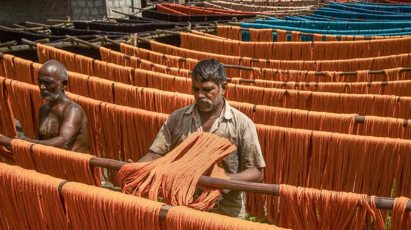 Workers hang dyed yarn for drying under the sun as seen on the National Handloom Day at a textile mill, in Guntur, Andhra Pradesh. PTI Photo