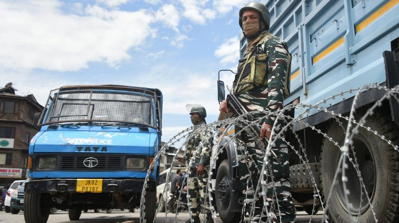 CRPF security personnel stand guard after markets opened partially in Kashmir. PTI photo