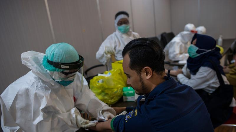 An Indonesian medical staff takes a blood sample from a woman during a rapid test in Surabaya on May 11, 2020 amid the COVID-19 coronavirus outbreak. AFP Photo