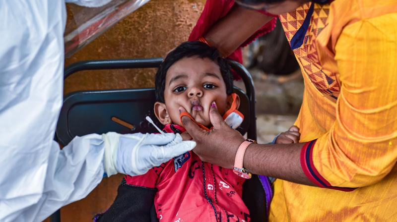 A health worker collects swab sample of a child for Covid-19 test, at majestic bus stand in Bengaluru. (Photo: PTI)