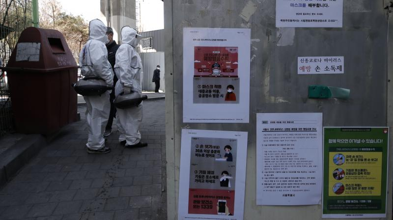 Workers wearing protective gears prepare to spray disinfectant near notices about precautions against new coronavirus in Seoul. (AP)