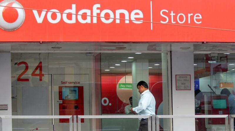 In this Jan. 20, 2012 file photo, a visitor walks in a Vodafone store in Bangalore. Vodafone Idea is in trouble over its payments to the Department of Telecom. (PTI)