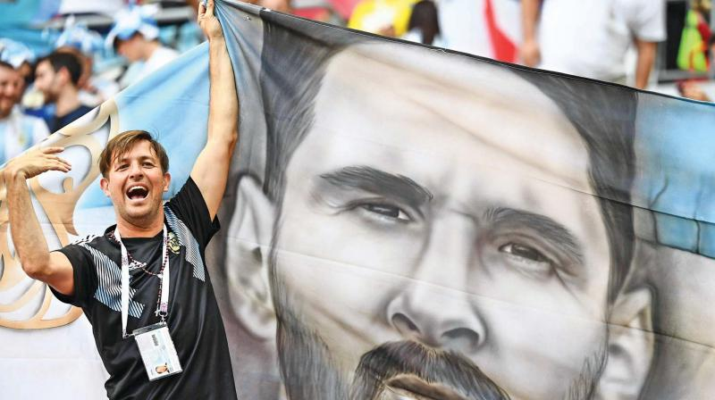 A fan holds a flag with a painting that resembles Lionel Messi at the Kazan Arena. (Photo: AP)