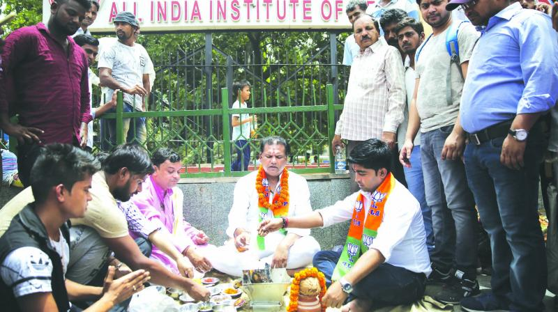 """BJP Yuva Morcha activists perform a """"havan"""" outside AIIMS, New Delhi, on Tuesday the long life and quick recovery of former Prime Minister Atal Behari Vajpayee. (Photo: AP)"""