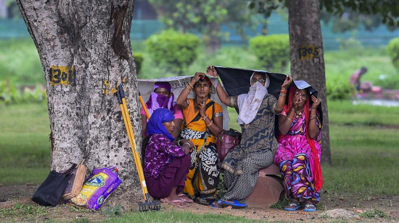 Women covers themselves with sheets during rain, in New Delhi. PTI Photo