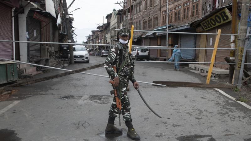An Indian paramilitary soldier stands guard by a closed road, as Kashmiris marked Eid during lockdown to curb the spread of coronavirus in in Srinagar. AP Photo