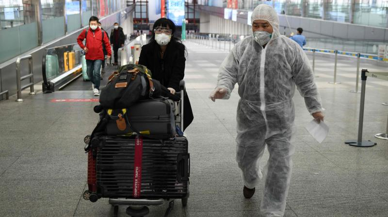 A man wears a protective suit as a preventive measure against the COVID-19 coronavirus as he accompanies a passenger leaving Beijing Capital Airport (AFP PHOTO)