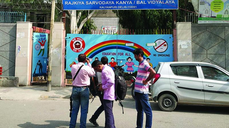 People gather outside the school in East Delhi on Saturday. — (Photo: Biplab Banerjee)