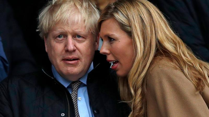 n this file photo taken on March 7, 2020 Britain's prime minister Boris Johnson (left) with his partner Carrie Symonds attend the Six Nations international rugby union match between England and Wales at the Twickenham in west London.  Boris Johnson and Carrie Symonds have named their son Wilfred Lawrie Nicholas Johnson in a tribute to their grandfathers and the doctors who helped save the prime minister's life. (AFP)