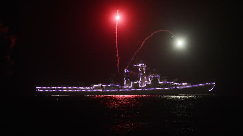 An illuminated Indian Navy warship release flares as a signal of gratitude to frontline medical staff fighting the COVID-19 pandemic off the Ramakrishna beach in Visakhapatnam on Sunday, May 3, 2020. (DC Photo: K Murali Krishna)