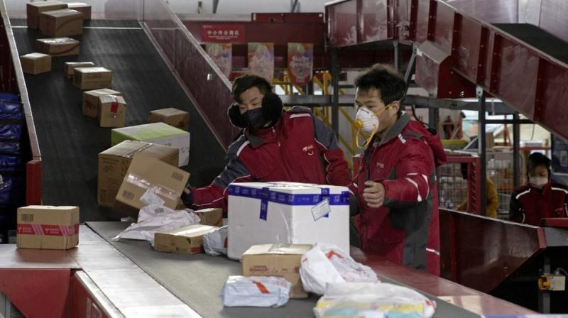 Photo shows delivery workers for Chinese e-commerce giant JD.com sort out parcels at a distribution center in Beijing, China. AP photo