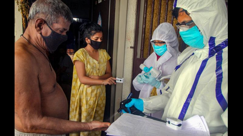 A health worker checks sanitises the hand of a man in Mumbai. (PTI)