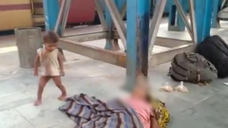The video grab shows the child trying to pull the blanket off his mother