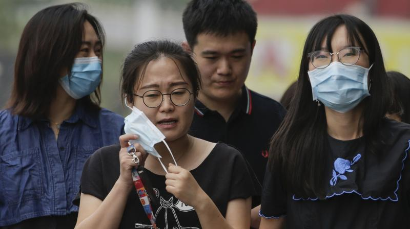 A woman takes off her face mask next to her colleagues wearing face masks to protect against the new coronavirus as they walk on a street in Beijing. (AP)