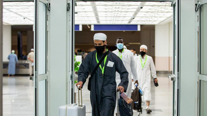 Travellers, mask-clad due to the COVID-19 coronavirus pandemic, walking with luggage as part of the first group of arrivals for the annual Hajj pilgrimage, at the Red Sea coastal city of Jeddah's King Abdulaziz International Airport. - The 2020 hajj season, which has been scaled back dramatically to include only around 1,000 Muslim pilgrims as Saudi Arabia battles a coronavirus surge, is set to begin on July 29. (via AFP)
