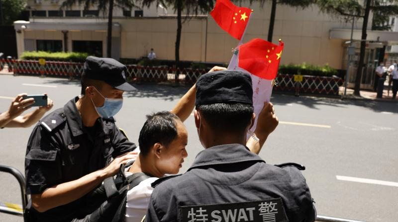 A Chinese man is taken away after shouting pro-China slogans outside the former United States Consulate in Chengdu in southwest China's Sichuan province on Monday, July 27, 2020. Chinese authorities took control of the former U.S. consulate in the southwestern Chinese city of Chengdu on Monday after it was ordered closed amid rising tensions between the global powers. (AP)