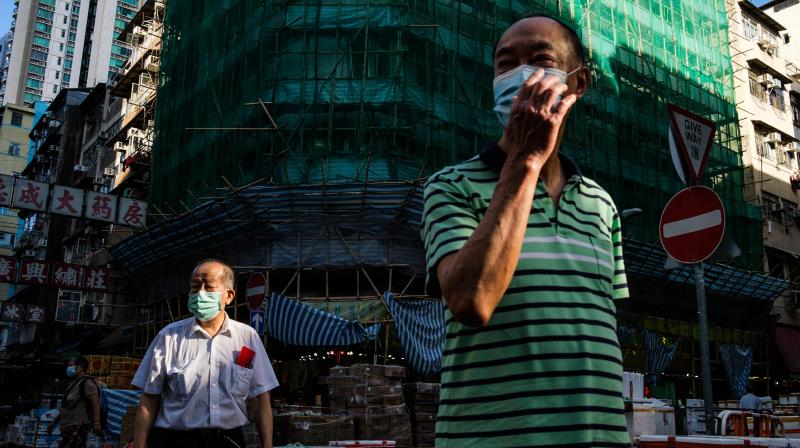 Pedestrians wear face masks in the Kowloon-side Sham Shui Po district of Hong Kong. (AFP)