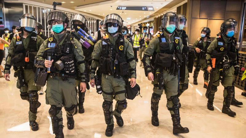 Riot police secure a shopping mall after prostesters gathered to mark one year since a group of white-clad men attacked pro-democracy protesters who were returning home from protests at the nearby Yuen Long train station, in Hong Kong. (AFP)