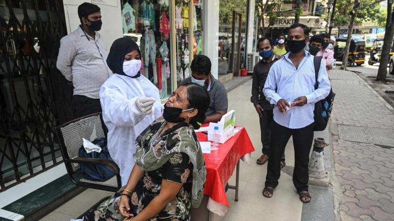 A health worker takes a swab sample for a Rapid Antigen Testing (RAT) at a roadside market following restrictions imposed by the state government amidst rising Covid-19 coronavirus cases, in Mumbai on April 6, 2021. (Indranil Muukherjee / AFP)