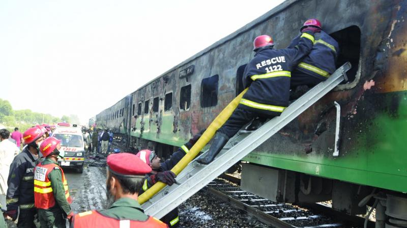 Rescue workers look for survivors following a train damaged by a fire in Liaquatpur area of Rahim Yar Khan district in Pakistan on Thursday. (Photo: AP)