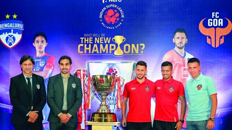 Bengaluru FC coach Charles Cuadrat, midfielder Dimas Delgado, Goa FC player Coro, captain Mandar Desai and coach Sergio Lobera pose with winners' trophy of the Indian Super League in Mumbai on Saturday. (Photo: PTI)