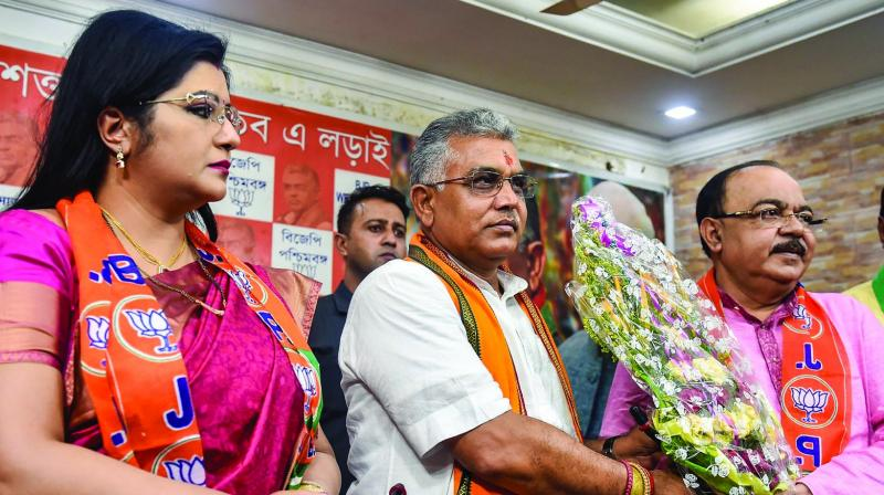 BJP MP and state president Dilip Ghosh felicitates former mayor of Kolkata Sovan Chatterjee as Prof. Baisakhi Chatterjee looks on, during an event at state party office, in Kolkata on Tuesday. (Photo: PTI)
