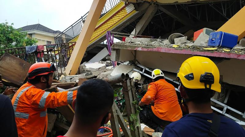 This handout photo taken and released on January 15, 2021 by Indonesia's National Disaster Agency shows rescuers looking for survivors trapped in a collapsed building in Mamuju, after a 6.2-magnitude earthquake rocked Sulawesi island. (Photo by Handout/ National Search and Rescue Agency / AFP)