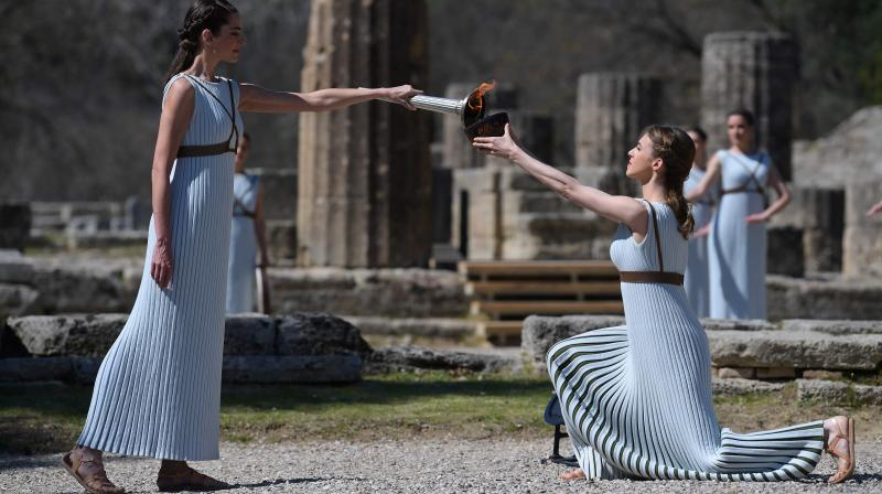 Women dressed as priestesses take part in the Olympic flame lighting during the Olympic ceremony in ancient Olympia on Thursday. AFP Photo