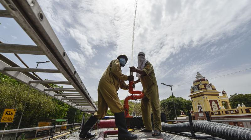 NDMC firefighters spray disinfectants on a street at Mandir Marg during a nationwide lockdown in the wake of coronavirus pandemic, in New Delhi. PTI photo