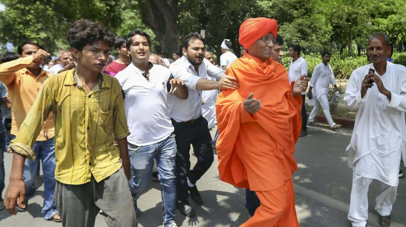 People push social activist Swami Agnivesh while he was on the way to pay tribute to former PM Atal Behari Vajpayee at Deen Dayal Upadhyaya Marg in New Delhi on Friday. Agnivesh was reportedly assaulted later. (Photo: PTI)