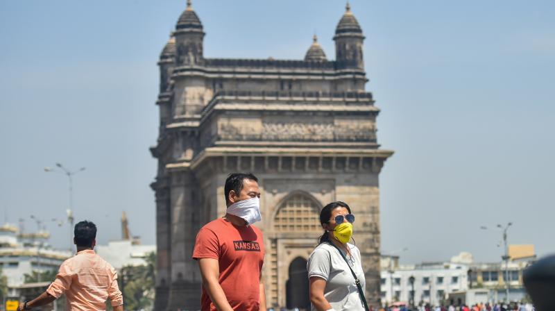Tourists wear protective masks in view of  coronavirus pandemic at Gateway of India in Mumbai. (PTI)