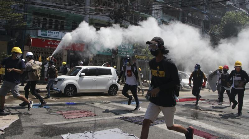 An anti-coup protester discharges a fire extinguisher to counter the impact of the tear gas fired by police during a demonstration in Yangon, Myanmar, Monday, March 8, 2021. Large protests have occurred daily across many cities and towns in Myanmar. (AP)