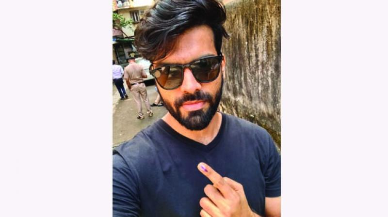 Shahid Pavte shows finger marked with indelible ink after casting vote at a polling station during Maharashtra Assembly polls in Mumbai.
