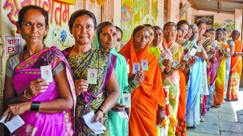 Voters display their identity cards as they wait in a queue to cast their votes for the Maharashtra Assembly polls in Sangli on Monday. (Photo: PTI)