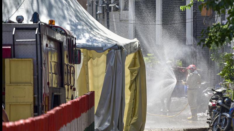 Firefighters spray disinfectant near Nizamuddin mosque in Delhi. PTI Photo