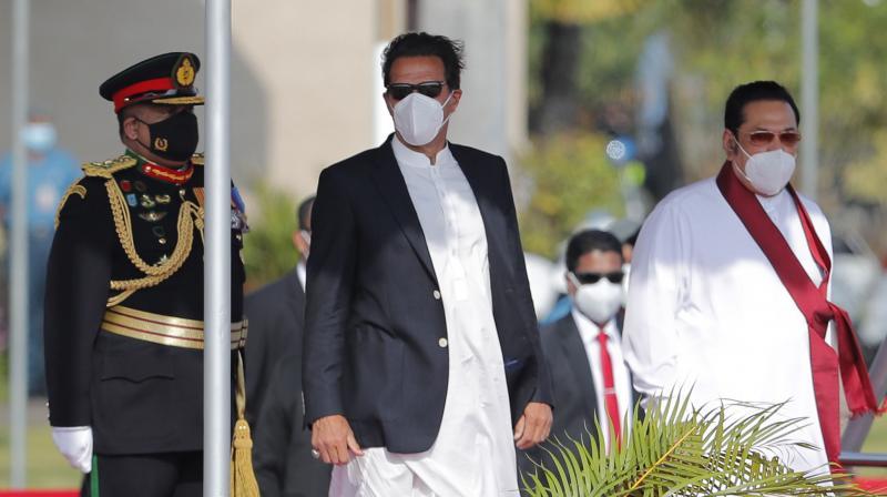 Pakistan Prime Minister Imran Khan, center, stands with Sri Lankan Prime Minister Mahinda Rajapaksa, right, after his arrival in Colombo, Sri Lanka, Tuesday, February 23, 2021. Khan arrived in Sri Lanka for a two day official visit. (AP/Eranga Jayawardena)