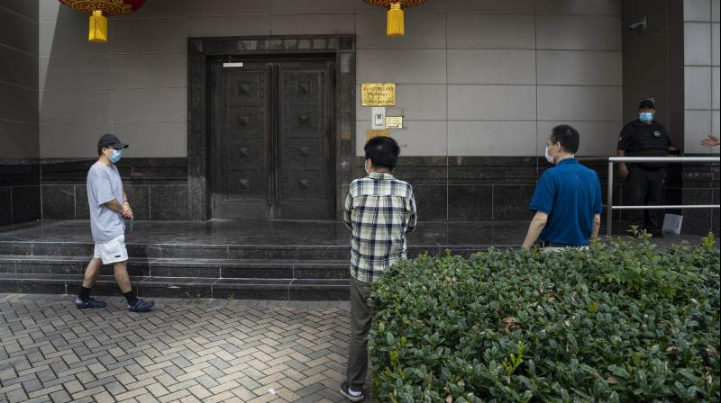 People walk around the Chinese consulate building in Houston while trying to gain access after the US ordered China to close its doors on July 22, 2020. According to the State Department, the Chinese consulate was ordered to close