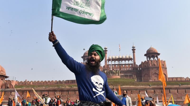A farmer waves a flag along with others as they gather at Red Fort during their tractor parade on Republic Day, in New Delhi, Tuesday, January 26, 2021. Farmers have been agitating against new farm laws. (PTI/Arun Sharma)