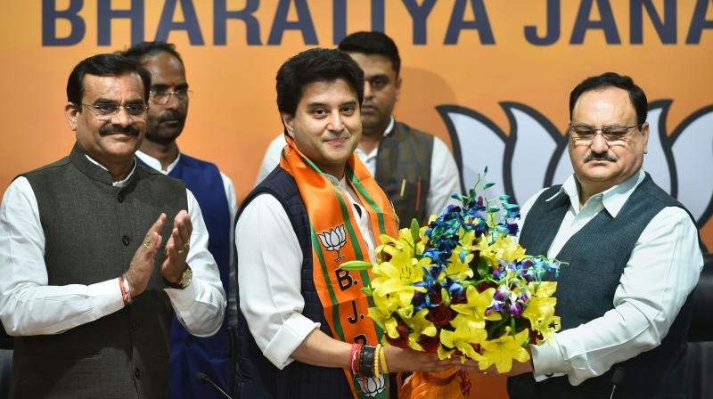 Congress leader Jyotiraditya Scindia is welcomed as he ajoins BJP in presence of party President JP Nadda (R), at BJP headquarters in New Delhi, Wednesday. PTI photo