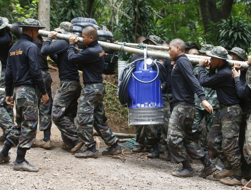 Soldiers carry a pump to help drain the rising flood water. (Photo: AP)