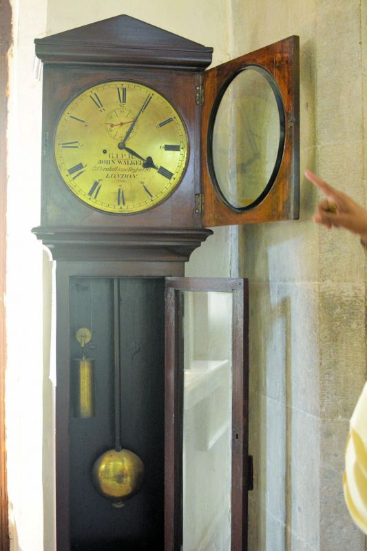 A 100 plus year old clock is lined with Roman and Devnagiri  numerals.