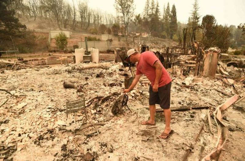 A person looks at what remains of his burned home during the Carr fire in Redding, California on July 27. (Photo: AFP)