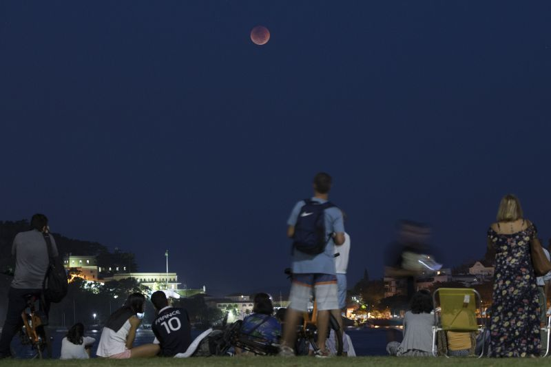 People watch a blood moon as it rises in Rio de Janeiro, Brazil, on Friday. (Photo: AP)
