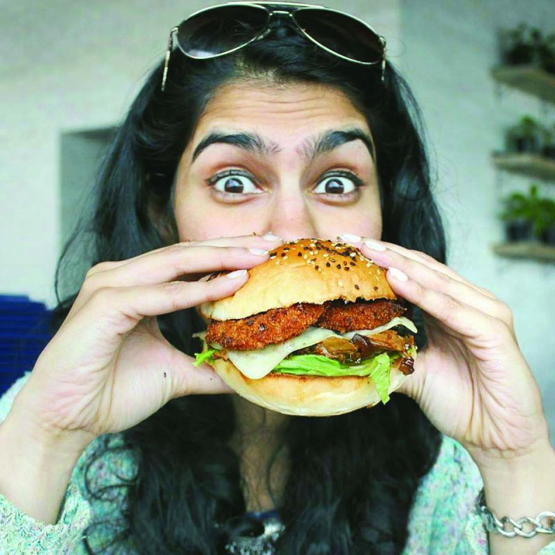 Carolyn, a foodie, poses with a healthy Quinoa burger