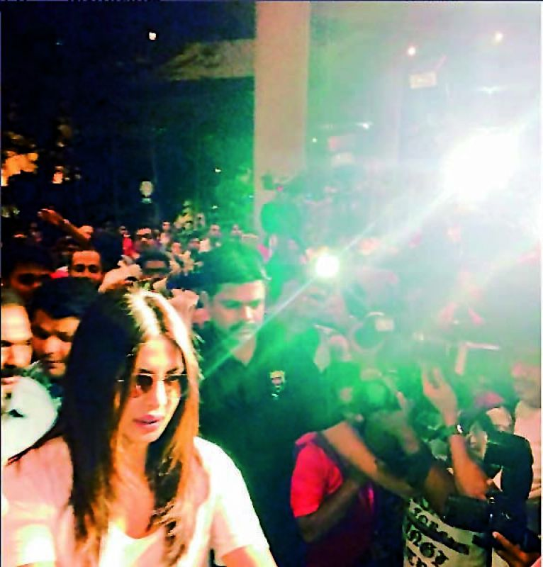 A picture showing PeeCee being mobbed at the Mumbai  airport, after she returned to India from the US